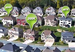 An aerial view of a neighborhood with home value indicators.