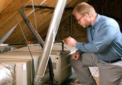 A licensed home inspector in a home's attic evaluating the HVAC system.