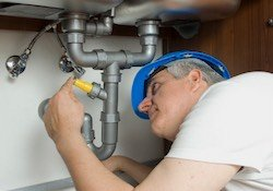 A licensed plumber repairing a leak under the kitchen sink.