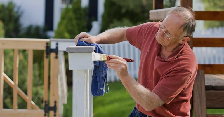 A man painting a deck railing in preparation to sell his home.