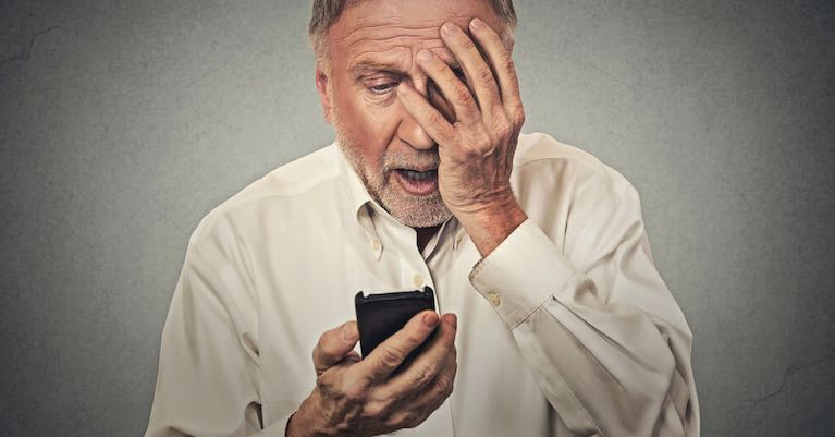 An older man viewing a lowball purchase offer for his home on his cell phone.