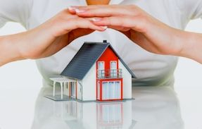 A woman's hands over a home symbolizing the protection available from Metro Brokers insurance.