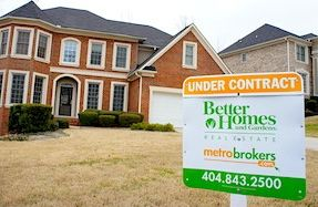 Beautiful two story brick home with BHGRE Under Contract sign in the front yard.