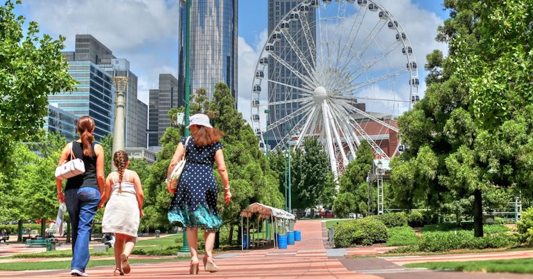 People walking to an Atlanta attraction with a view of the city's skyline.