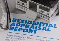 A completed residential appraisal report sitting on a desk.