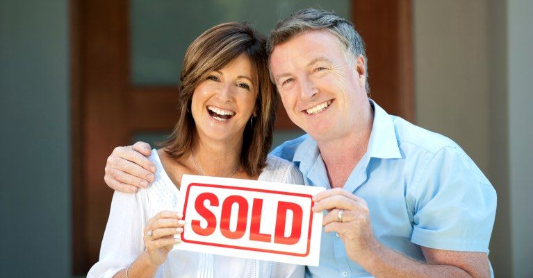 Happy couple holding SOLD sign in front of new home.