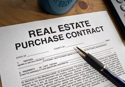 A blank real estate purchase contract on a desk.