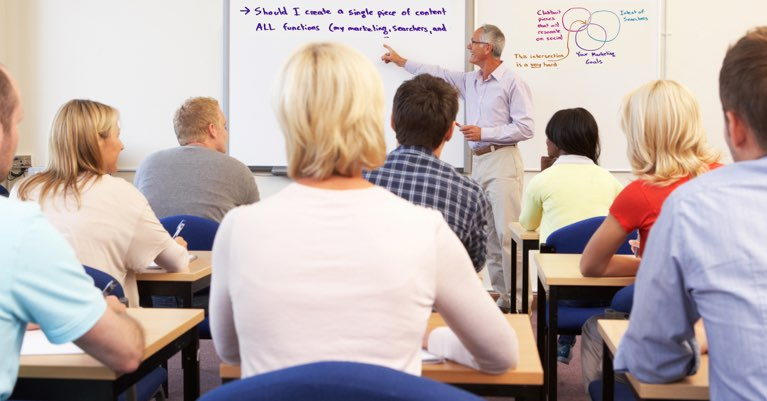 A teacher in front of a class of students taking a real estate course.