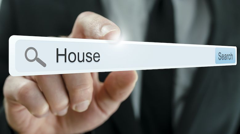 A hand touching an online search bar with the keyword, house.