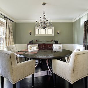 Staged dining room with round table and buffet.