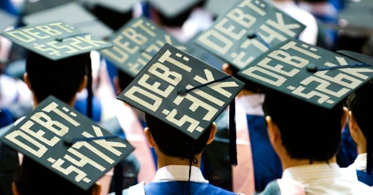 College students at graduation with student loan amount on their caps.