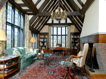 Formal living room with high ceilings and a fireplace in a Tudor style house.