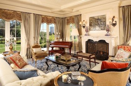 Lavishly decorated living room with fireplace in a Victorian style house.