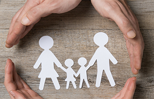 4 hands around a paper cutout family with 2 adults and 2 kinds - Coldwell Banker Paradise