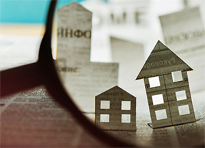 Magnifying glass looking at pictures of paper houses - Coldwell Banker Paradise