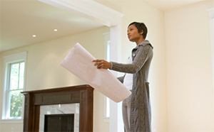 Woman inside house with house plans - Coldwell Banker Paradise