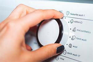 Hand on washing machine knob - Coldwell Banker Paradise