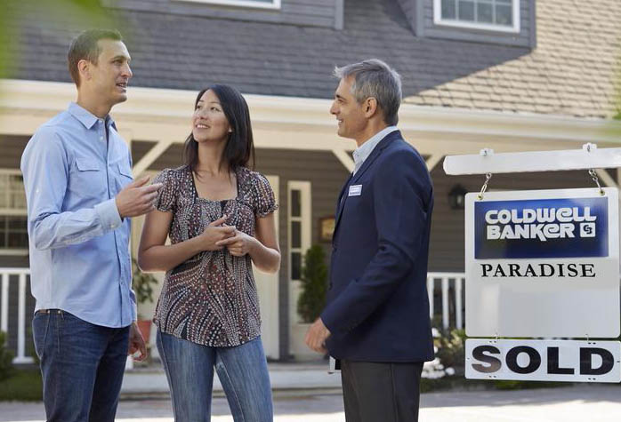Couple with coldwell banker realtor outside of sold house