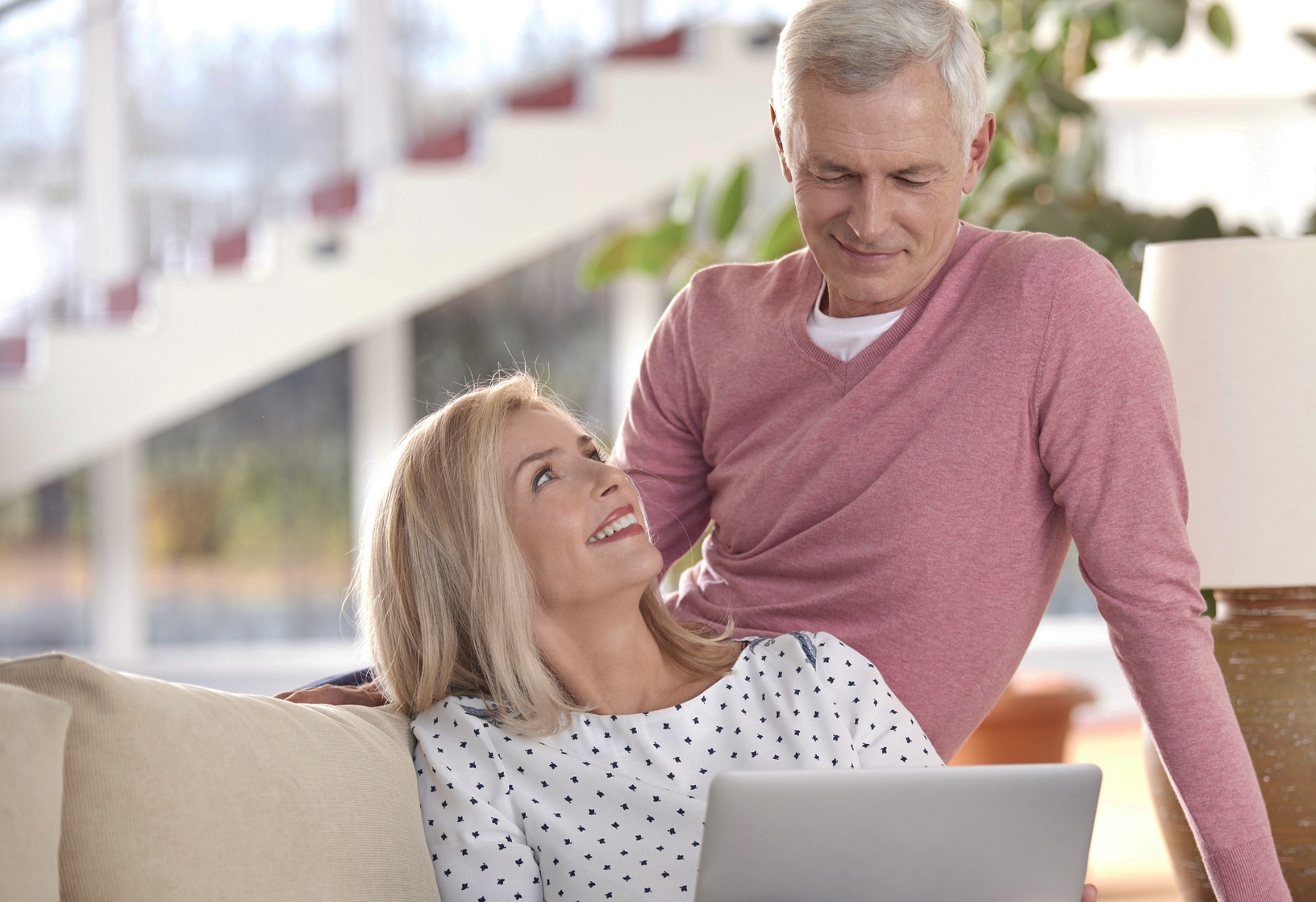 Older couple on couch looking at a laptop Coldwell Banker Paradise