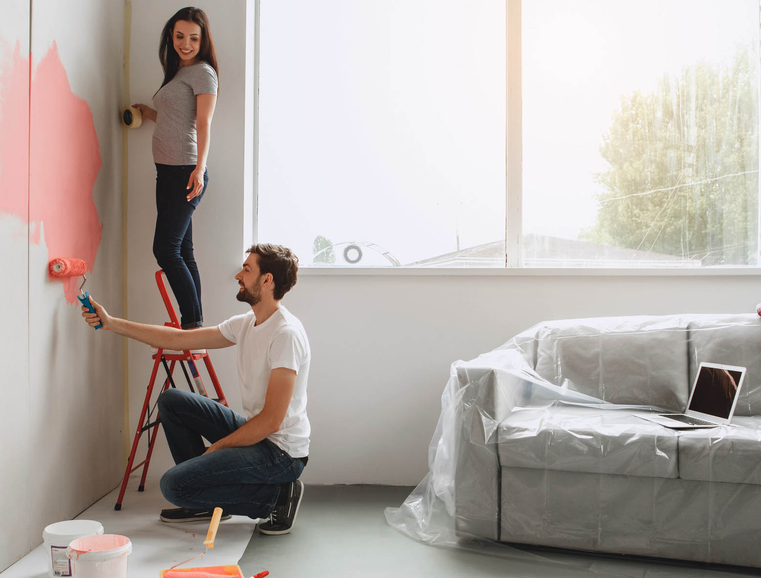 Couple painting a room pink Coldwell Banker Paradise