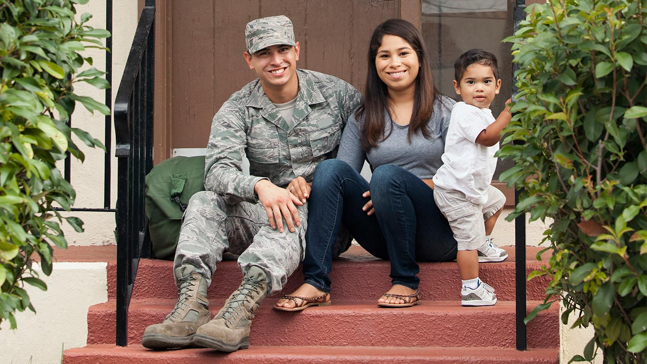 Military Home Buyers Sitting on Front Steps of Their New Home