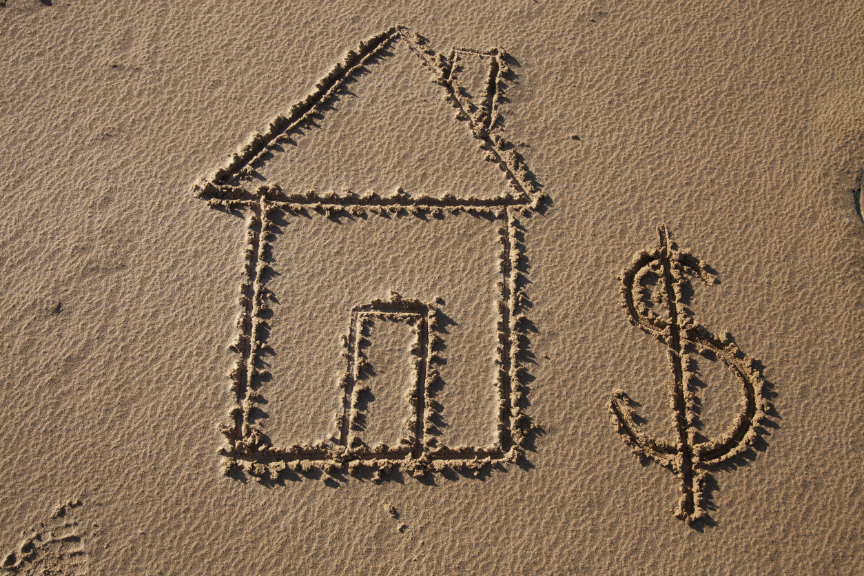 Home and Dollar Sign drawn in Beach Sand