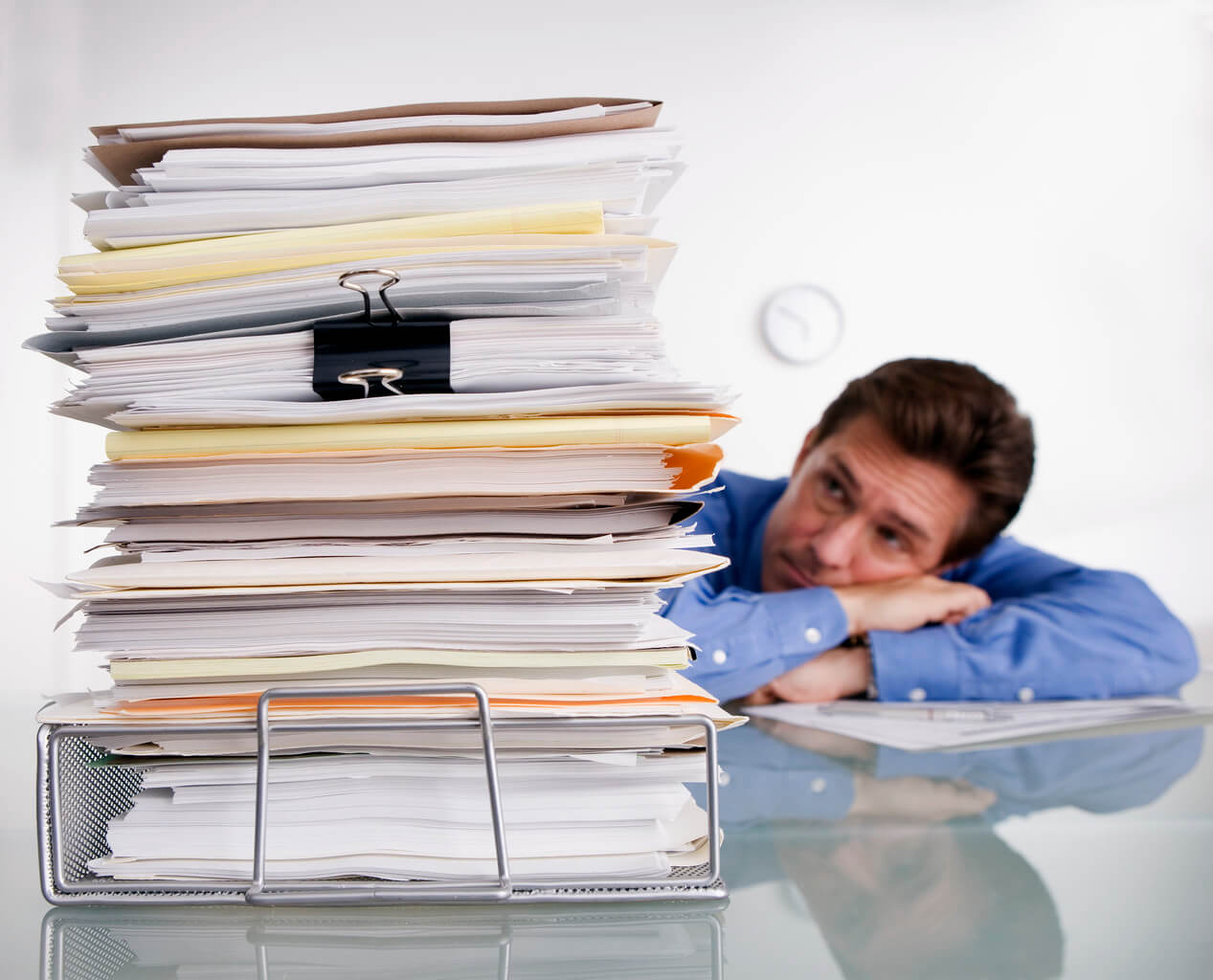 Overworked person leaning on desk buried in papers