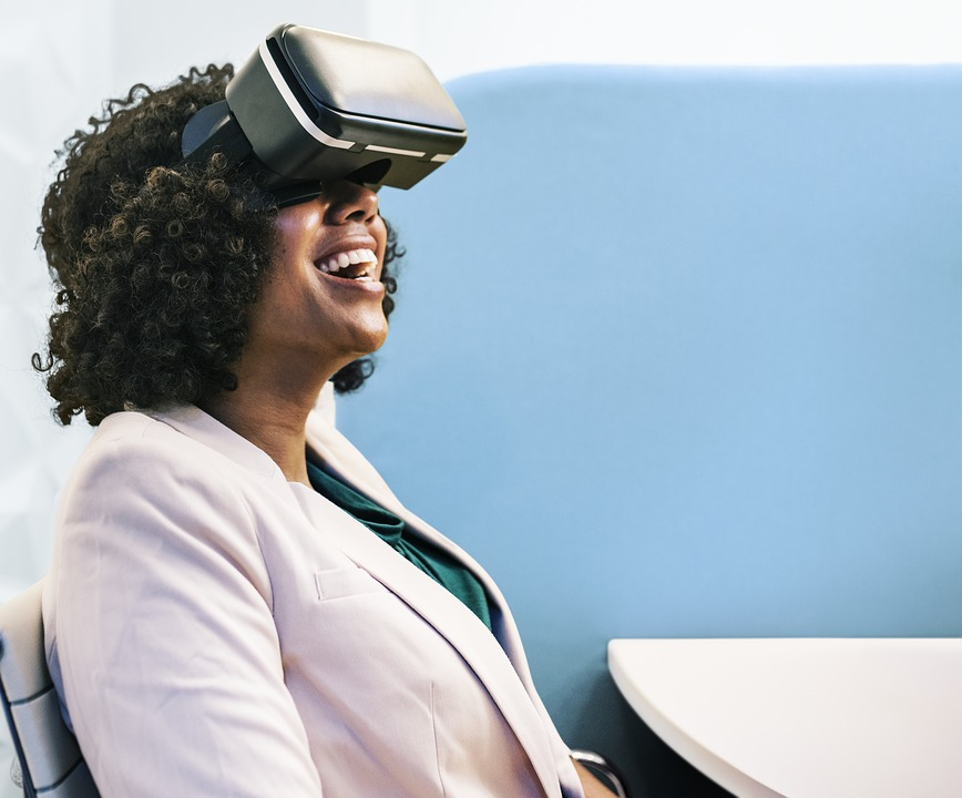 A woman in a professional suit, sitting at a desk, wearing a virtual reality headset, looking up and smiling.