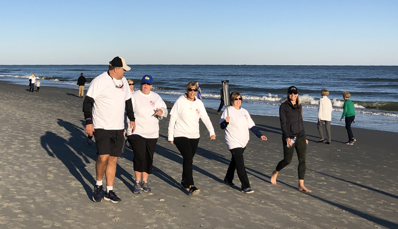 CRG Companies and Living Dunes group walk together on beach