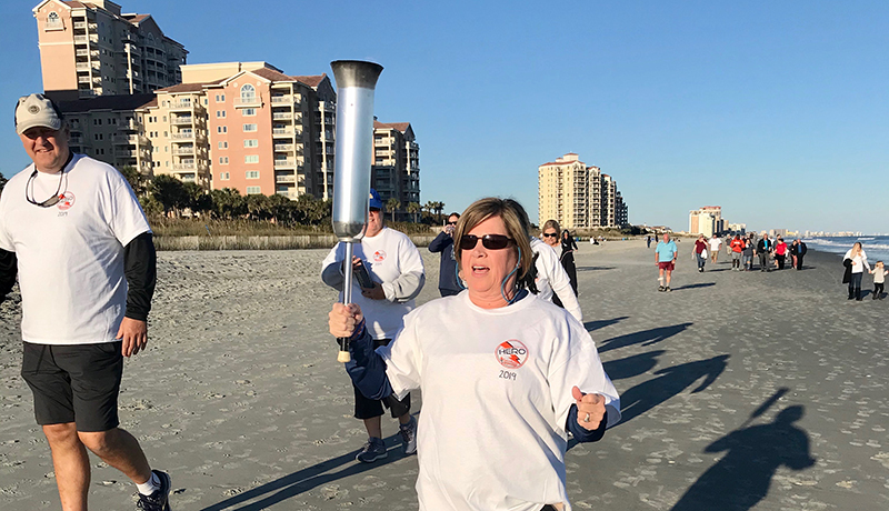 Terri Nardslico of CRG Companies and Living Dunes carrying 2019 Torch at Relay Beach Walk
