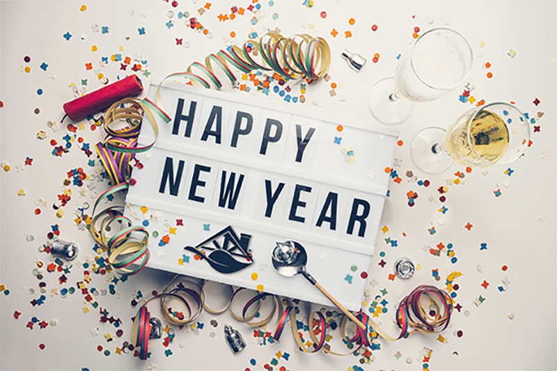 white sign black lettering happy new year with confetti champagne glasses and noise makers