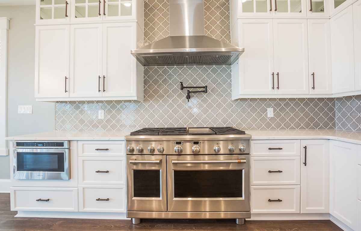 stainless steel kitchen appliances with scalloped subway tile